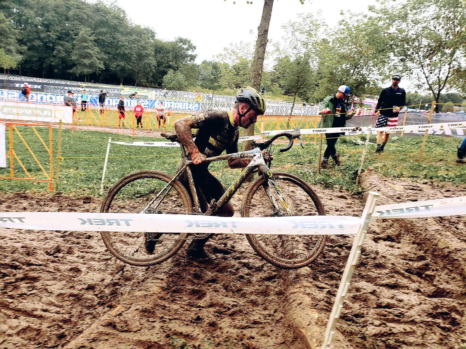 A cyclocross racer carries his bike up a muddy stair set at the Trek CX Cup in 2019.