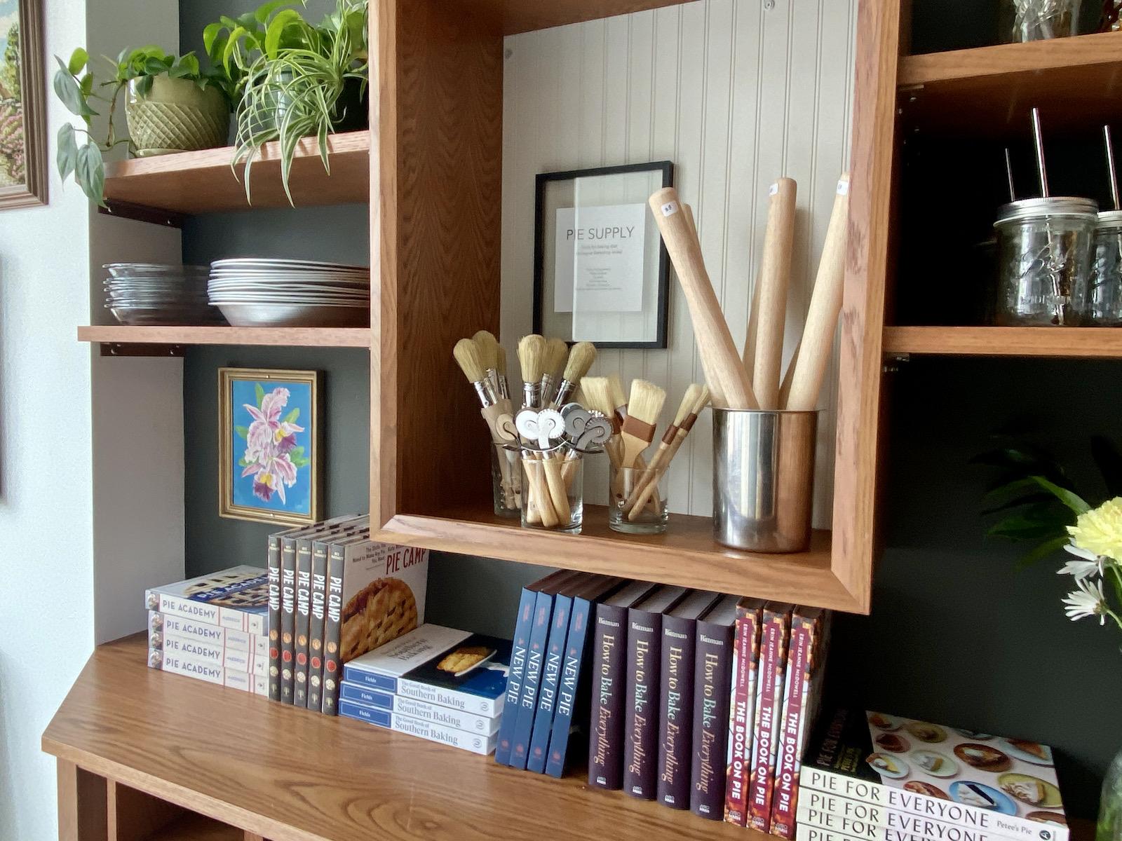 Pie supplies, cookbooks, plants on shelves