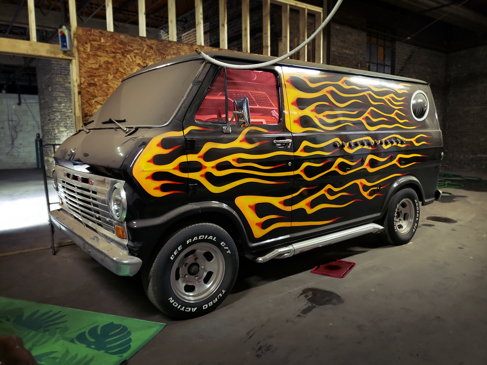 A black van with hot rod flames painted all across its exterior.