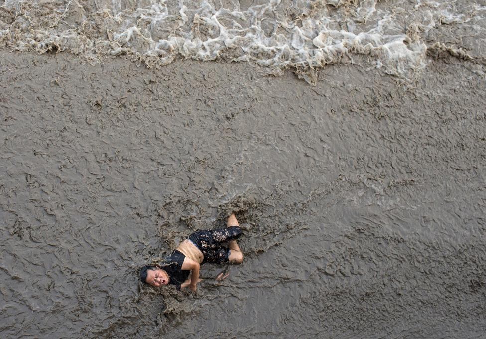 A man who fell off a bridge while waiting to watch tidal wave struggles as waves come towards him, on the banks of Qiantang River in Hangzhou, Zhejiang province, China, July 25, 2016. REUTERS/Chance Chan