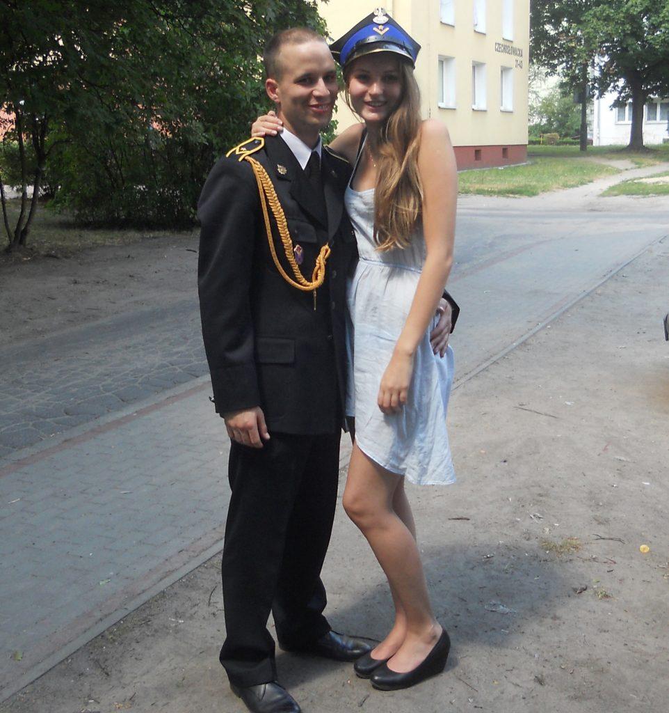 Zdjęcie Maćka i Moniki pozujących do zdjęcia. Uśmiechnięci. Maciek w mundurze, Monika w sukience.