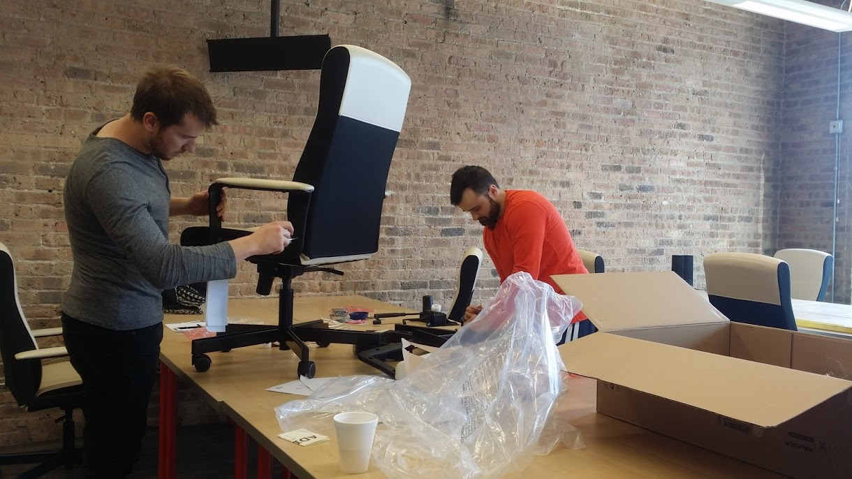 A photograph of two Packback team members building desk chairs.