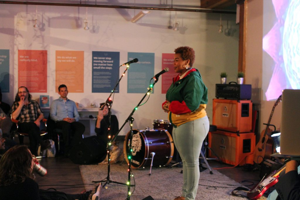 A photograph of a poet performing at Makespace, Packback's music and art event.