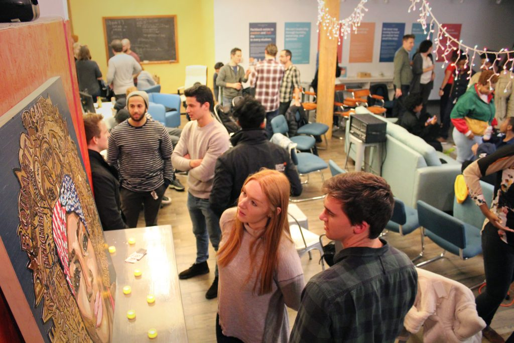 A photograph of people admiring artwork at Makespace, Packback's music and art event.