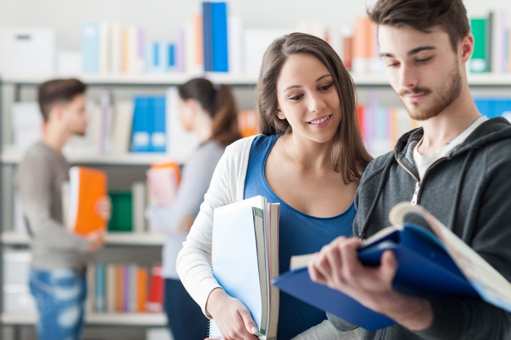 This is an image of two students discussing something they are reading in a book. Happy smiling students in the school library, they are holding books and studying together, friendship and learning concept