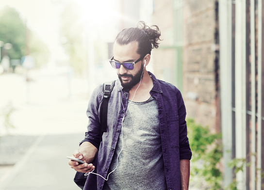 A man walking along a street looking at a mobile phone