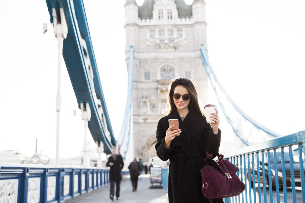 A woman walking across Tower Bridge in London, using a mobile phone and holding a cup