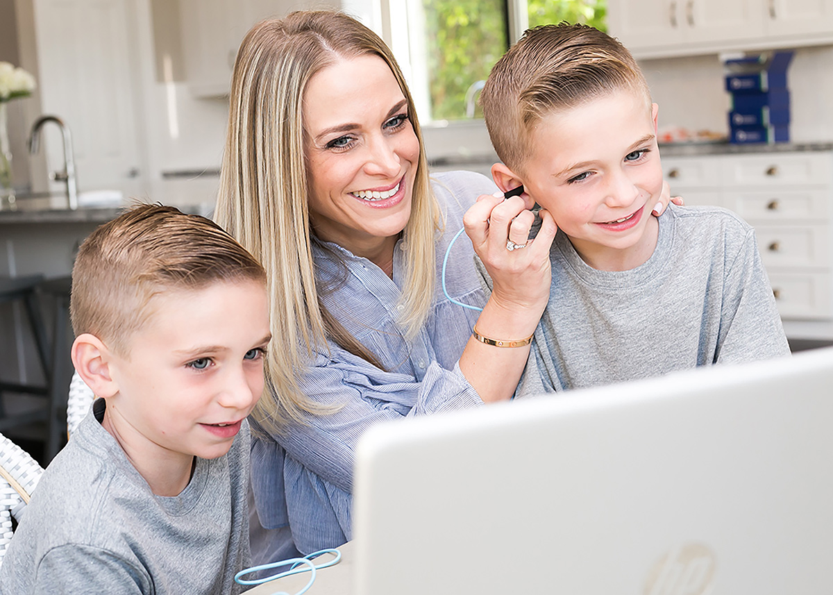 happy children and parent in need of urgent care exam using otoscope on a laptop