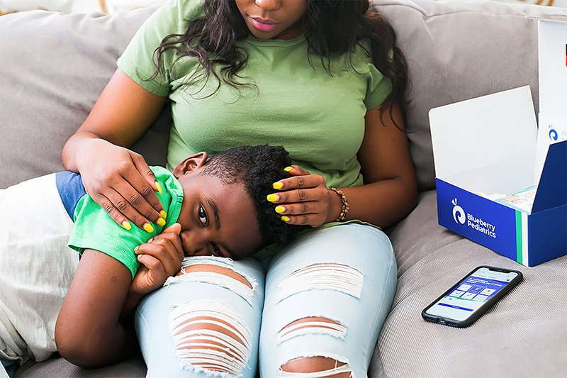Mom comforting sick child while answering questions about the child's symptoms in the Blueberry Pediatrics app