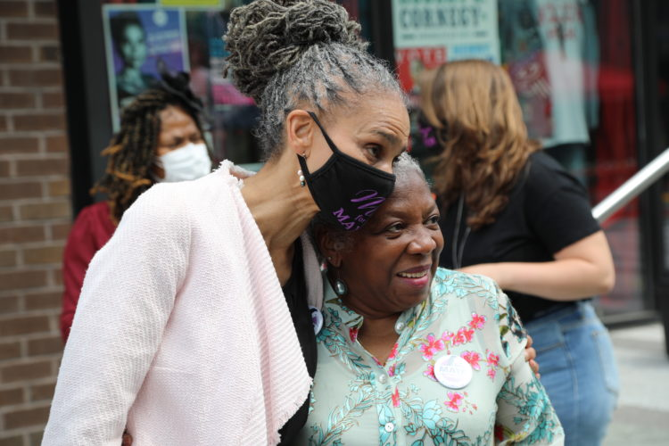 Maya Wiley, in a mask, takes a photo with an older woman
