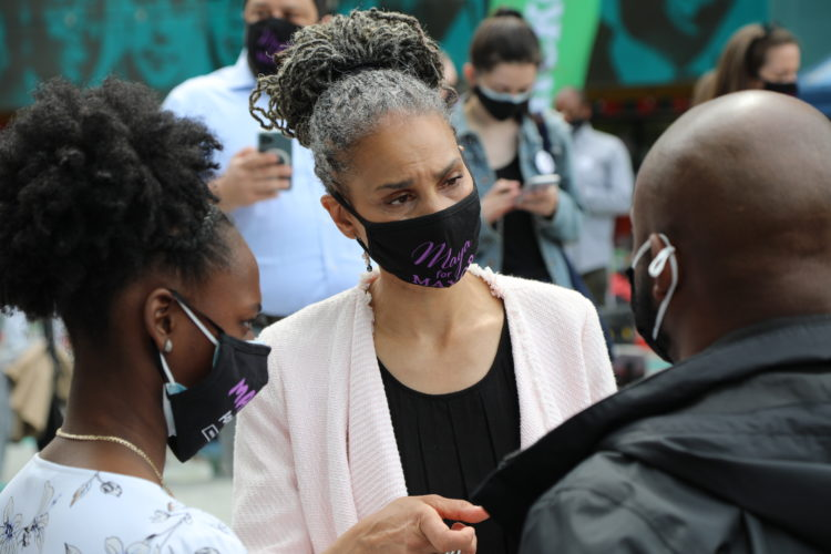 Maya Wiley, in a mask, listens to a member of the community