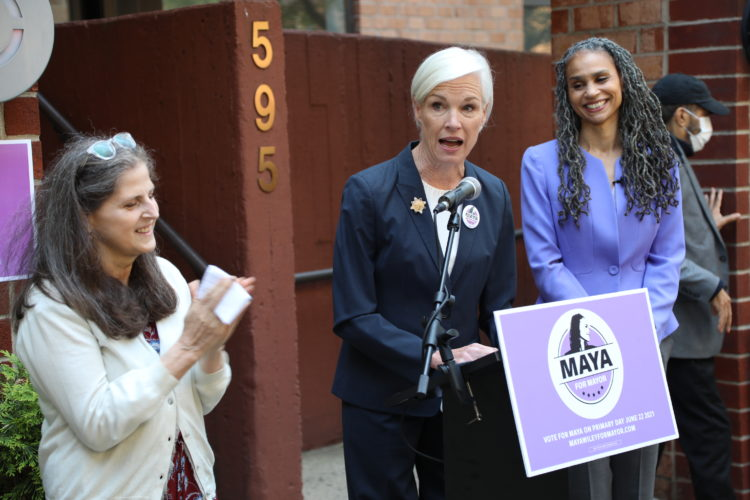 Maya Wiley looks on, smiling, as Cecile Richards Speaks at a podium