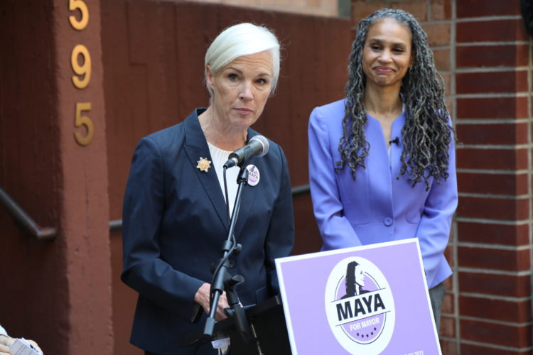 Maya Wiley looks on as Cecile Richards speaks at a podium