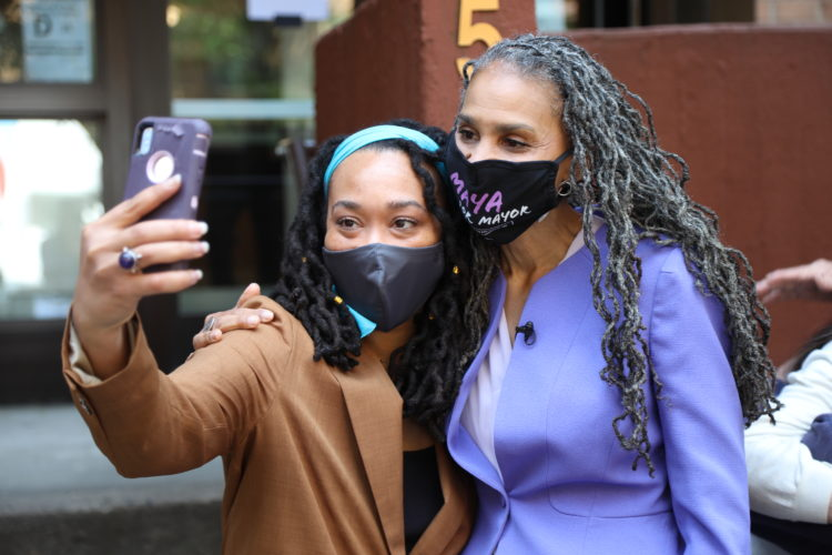 Maya Wiley, in a purple blazer, takes a selfie with a supporter