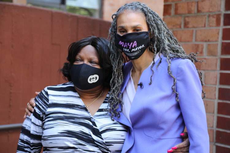 Maya Wiley, masked, takes a photo with a supporter