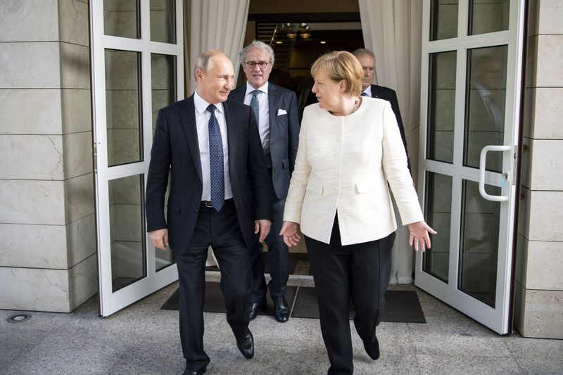 Germany Merkel hosts Russia Putin in marriage of convenience made by Trump