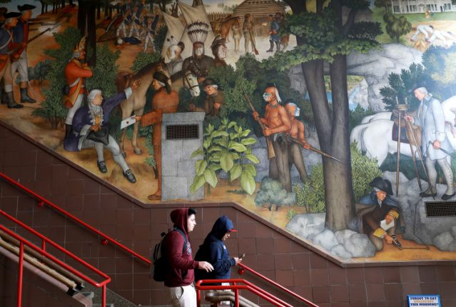 In this photo taken April 3, 2019, a pair of students walk past a historic mural that includes slaves and a dead Native American at George Washington High School in San Francisco. The San Francisco school board unanimously voted Tuesday, June 25, 2019, to destroy a controversial mural displayed in a public high school.