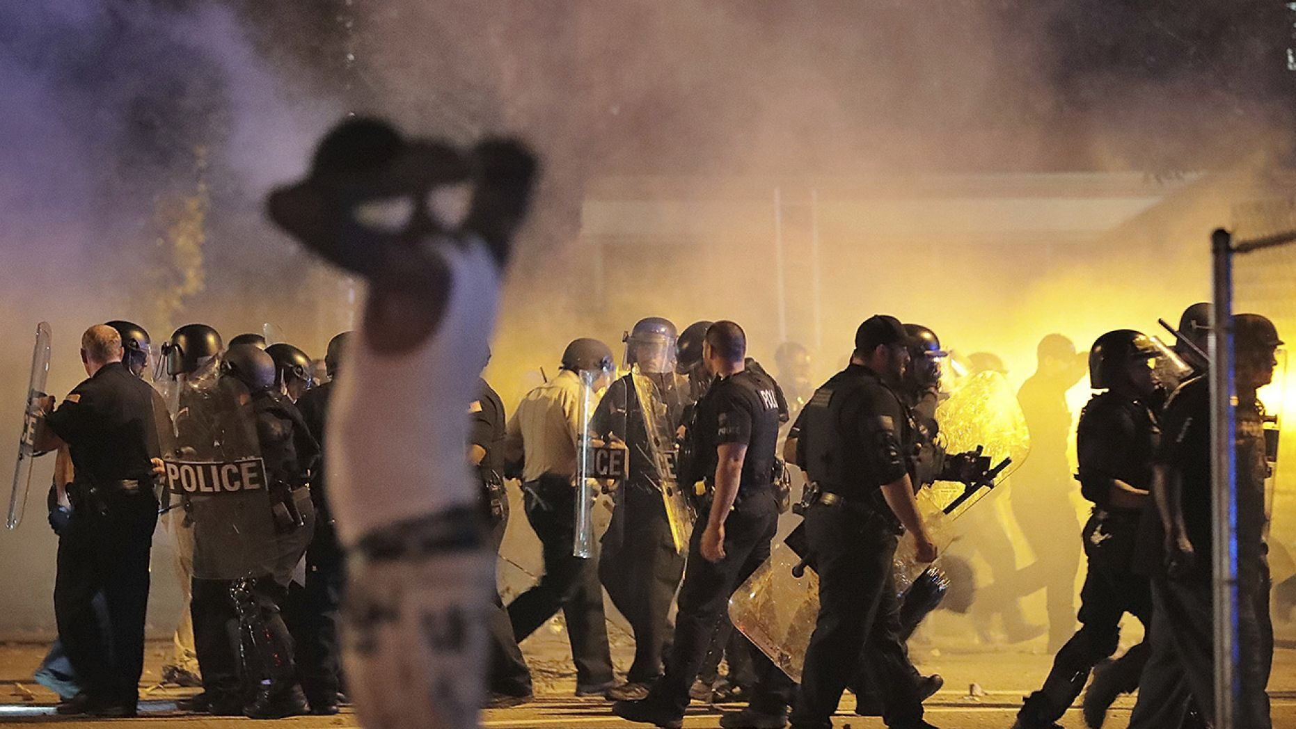 Police retreat under a cloud of tear gas as protesters disperse from the scene of a standoff after Frayser community residents took to the streets in anger against the shooting of a youth by U.S. Marshals earlier in the evening, Wednesday, June 12, 2019, in Memphis, Tenn.