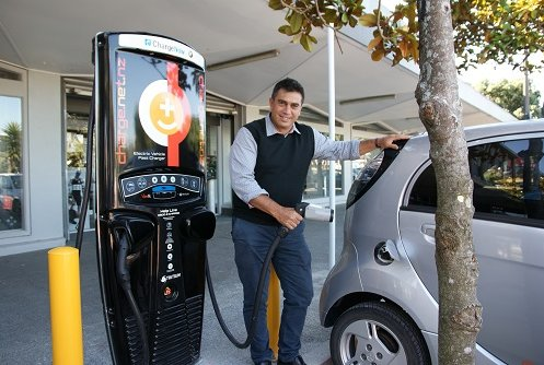 Mayor Mike Tana using a vehicle charging station.