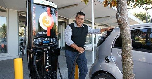 Mayor Mike Tana using a vehicle charging station.