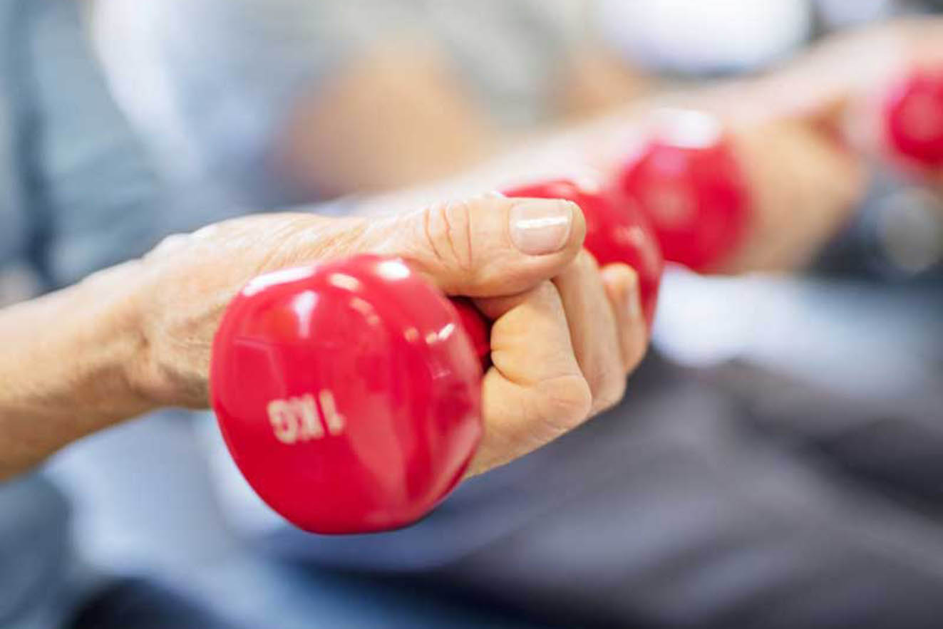 A senior holding free weights