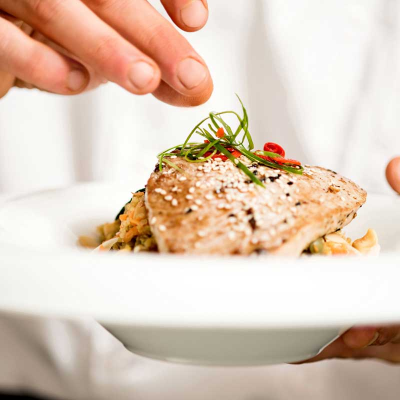 A close up photo of a chef adding garnish to a plated meal