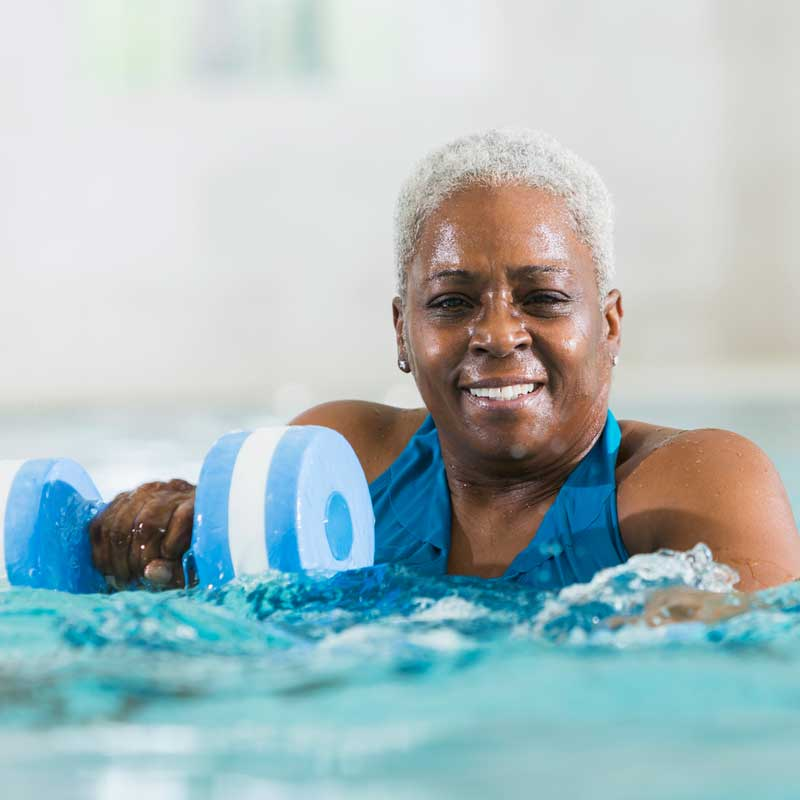 A senior woman uses weights while swimming in a pool