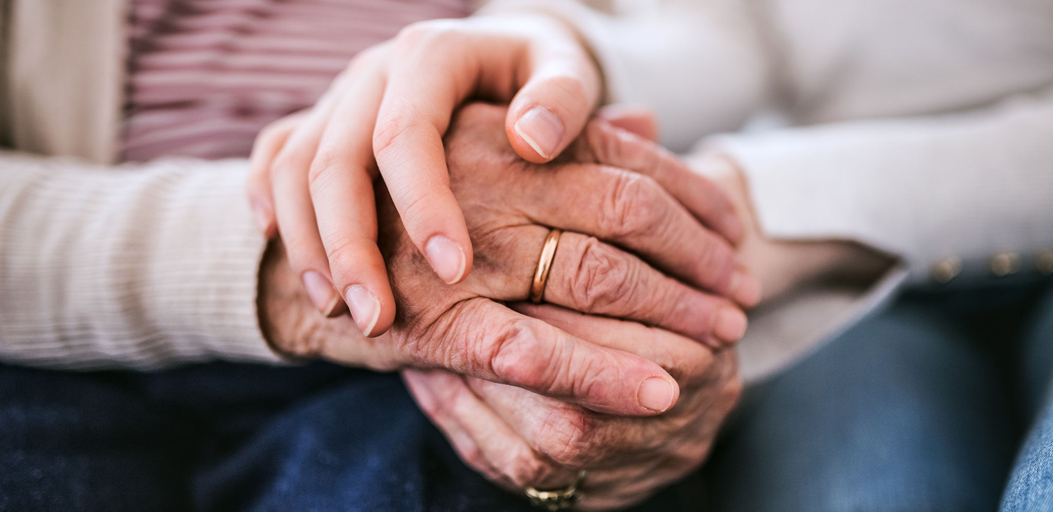 A close up photo of one pair of hands clasping another set of elderly hands