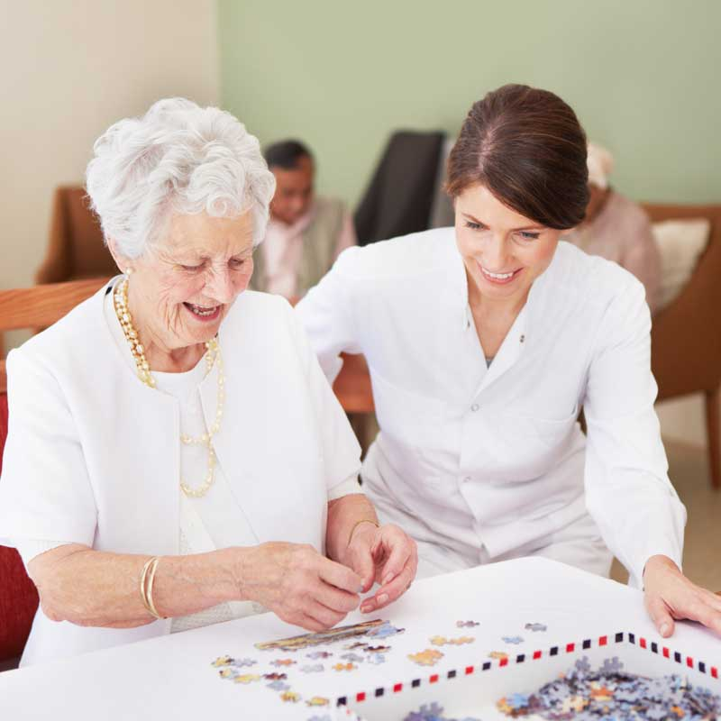 A memory care staff member works on an art project with a senior woman with memory loss