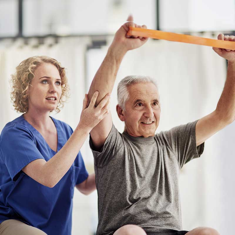 A physical therapist helps a man practice exercises