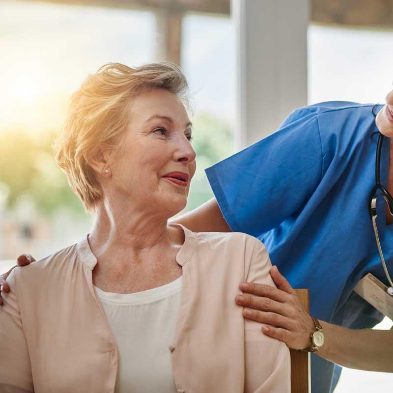 A nurse checks in on a senior woman sitting in a wheelchair