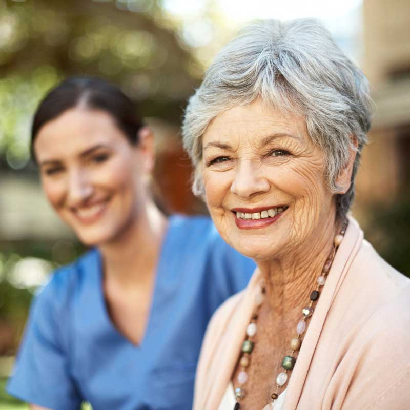 A senior woman and her health care professional pose for a photo
