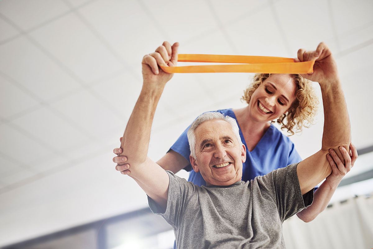 A senior man uses a resistance band with the guidance of a physical therapists