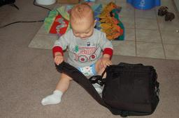Calvin sports training pants while playing with daddy's camera bag