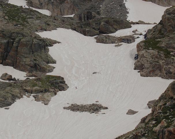 Skier descends snowfield below Apache Peak
