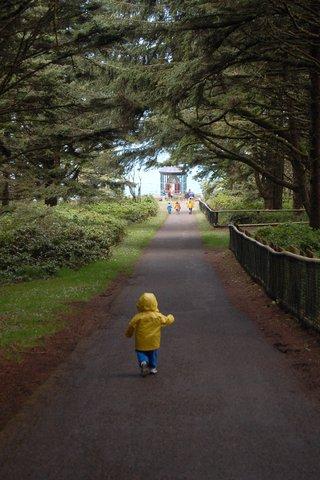 Calvin runs down the path toward the Cape Meares Lighthouse