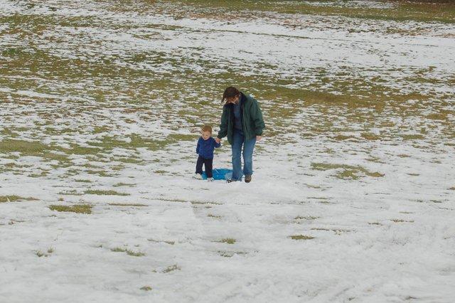 Calvin and Kiesa climb the hill after sledding