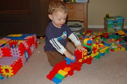 Calvin pushes a Duplo train over a viaduct
