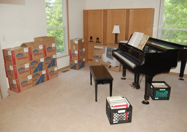 Boxes, bookshelf, and piano staging in the living room