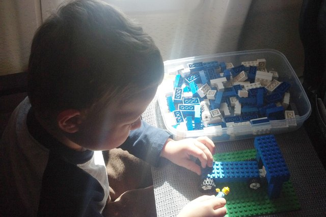Calvin plays with Legos on the plane to Pasco