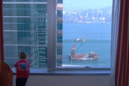 Calvin looks out the hotel window at Victoria Harbour