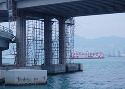 Bamboo scaffolding under an expressway suspended over Victoria Harbour