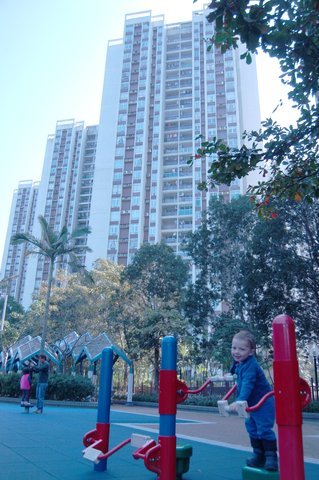 Calvin plays in the shadow of a residential tower in Quarry Bay