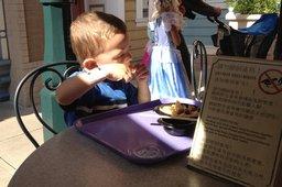 Calvin eats a Mickey Mouse waffle at Hong Kong Disneyland