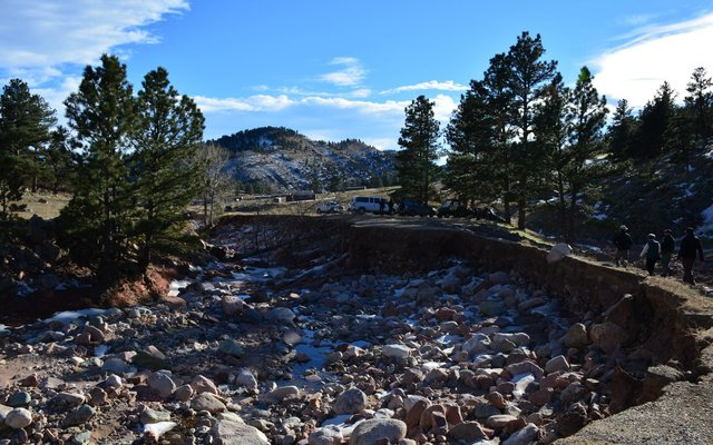 Flood tourists walk past damaged road at Heil Valley Ranch
