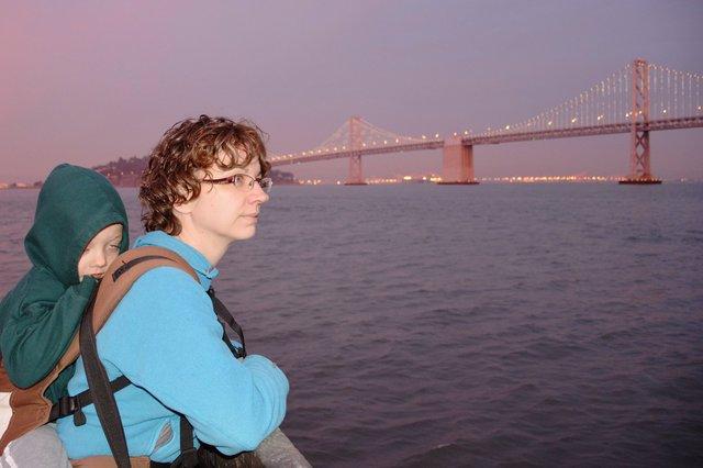 Kiesa and Calvin look out at the western span of the Bay Bridge at dusk