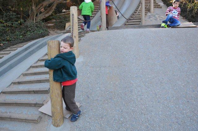 Calvin climbs down the concrete slide at Koret Children's Quarter Playground