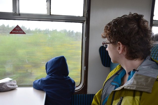 Calvin and Kiesa look out the window of the Strathspey Steam Railway at the Scottish countryside
