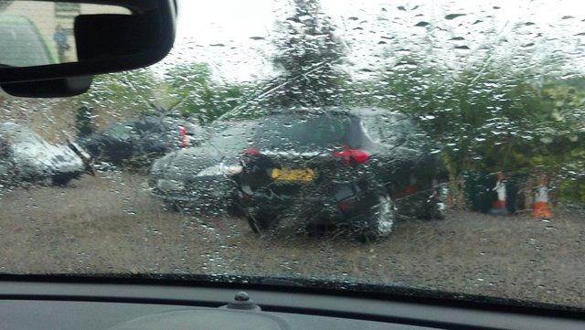 Rainy car park through a rental car windscreen