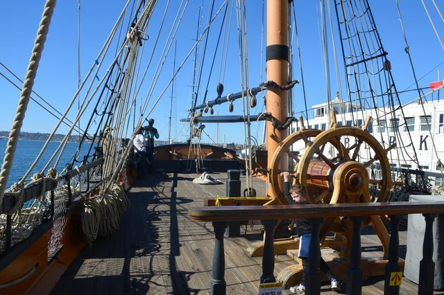 Calvin tries to turn the wheel of HMS Surprise